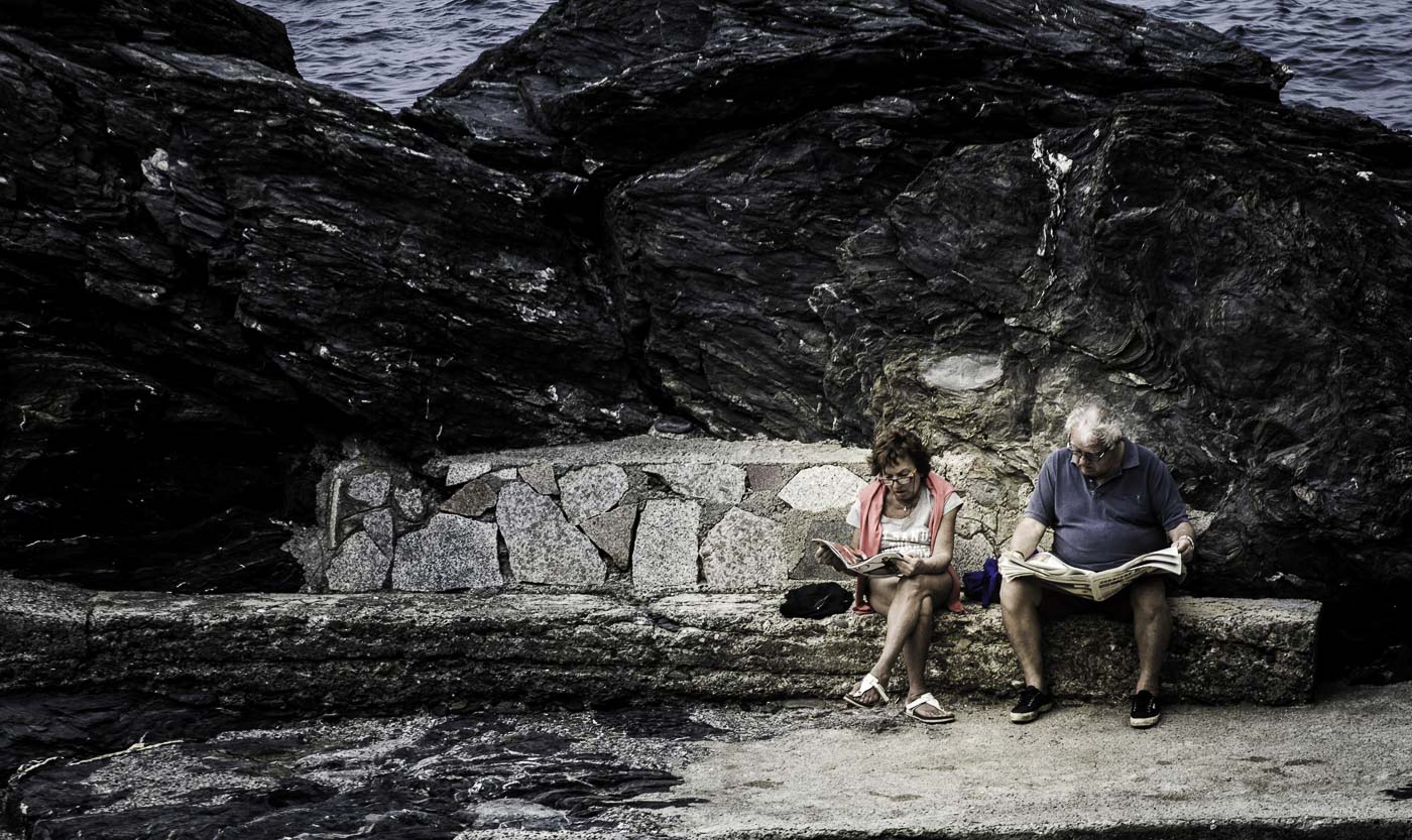 Old couple reading by the sea
